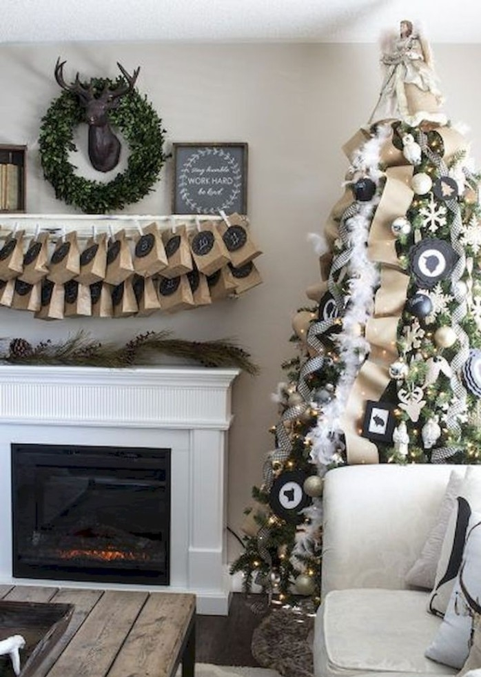 reindeer head decoration in black, surrounded by a green wreath, and an advent calendar, made from brown paper bags, hanging above a white and black fireplace
