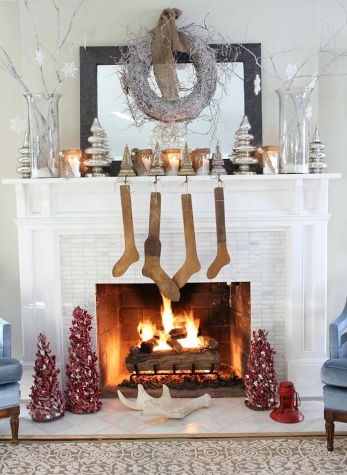rustic antique looking beige stockings, hanging on a white mantelpiece, decorated with silver ornaments, and lit candles,