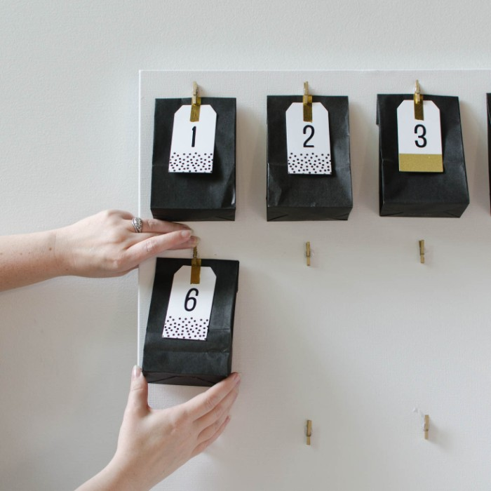 pair of hands, attaching a black paper bag, with a white label, featuring the number 6, onto a white board, fun advent calendars, more black paper bags attached above