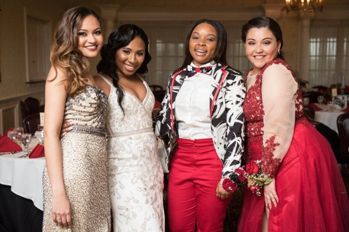 friends smiling at the camera, wearing smart outfits, beaded embroidered gowns, in pale beige and white, a red dress with lace, and sheer white sleeves, cocktail attire for women, red trousers with a white shirt, and a black, white and red jacket, worn with a matching bowtie