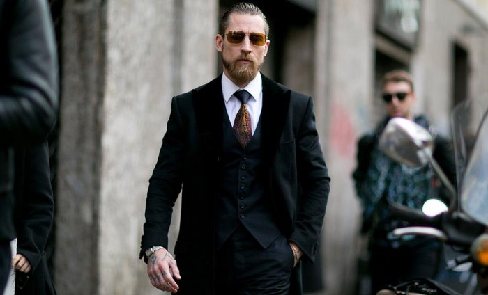 black tie optional, bearded man with dark yellow sunglasses, wearing a black three piece suit, with a white shirt, and a black and yellow tie