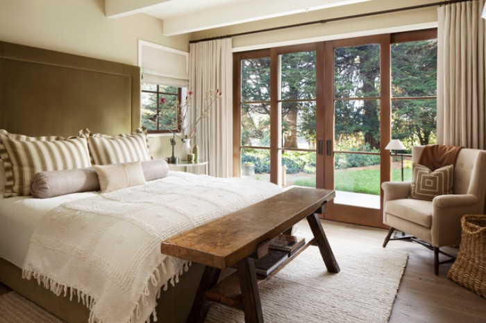 wooden bench and a pale beige armchair, in a bedroom with cream walls, a white ceiling, and a double bed, with a brown headboard