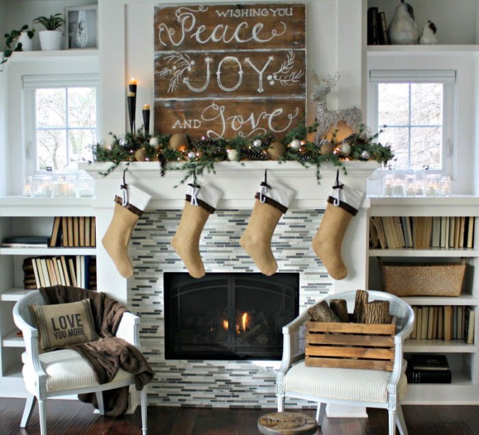 wishing you peace, joy and love, written in white, on a wooden board, placed above a fireplace, images of christmas, four beige stockings and lit candles