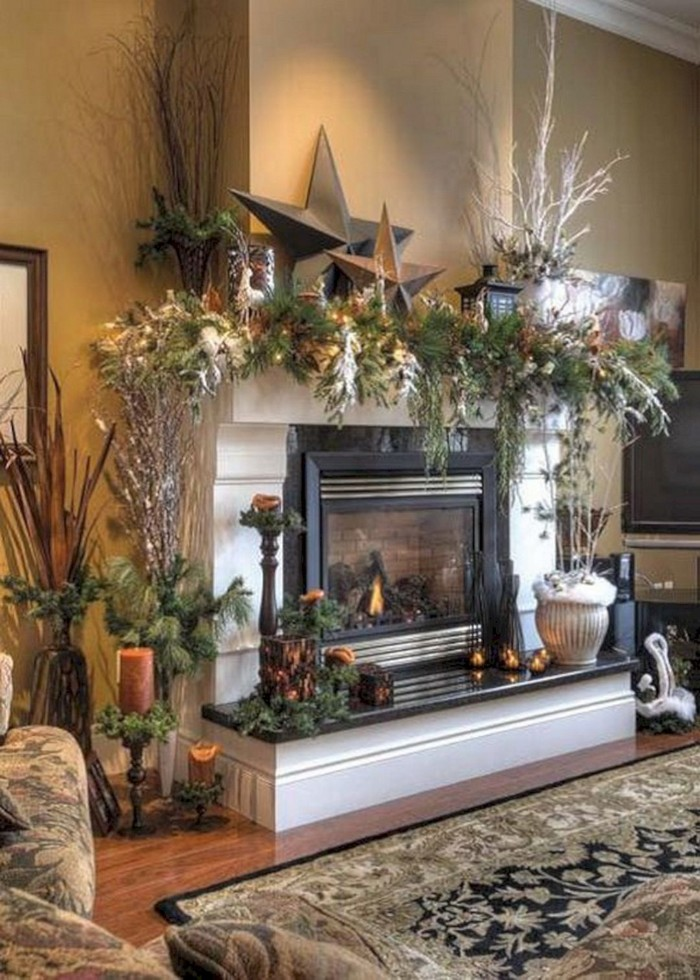 set of two beige star ornaments, one large and the other smaller, placed on a white mantel, decorated with a lush garland, made from pine branches, and other plants