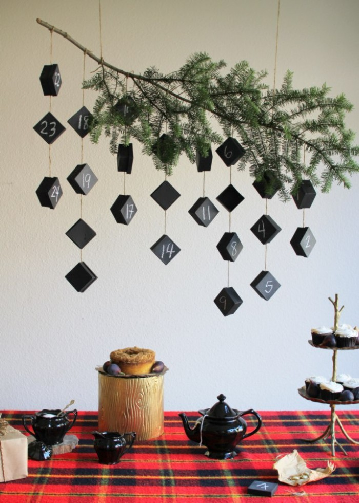 branch of a fir tree, decorated with several pieces of string, each tied to two or more, small black boxes, numbered with white chalk, advent calendar ideas, hanging over a table
