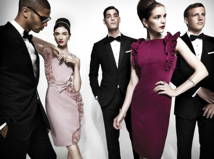 midi dresses in pale pink, and dark purple, with frills and a tie waist belt, worn by two slim brunette women, with hair styled in buns, cocktail attire for women, three men in black suits, white shirts and black bowties, standing next to them