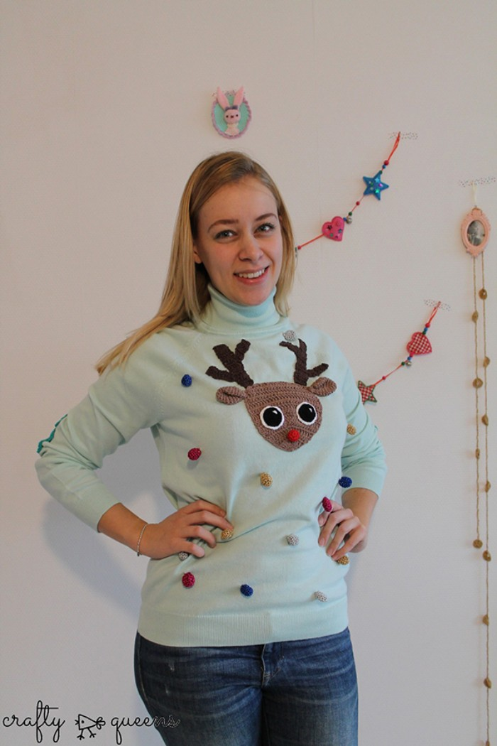 diy ugly christmas sweater, smiling blonde woman, dressed in a pale blue jumper, decorated with small pom poms, in different colors, and a brown crocheted deer's head, with a red nose