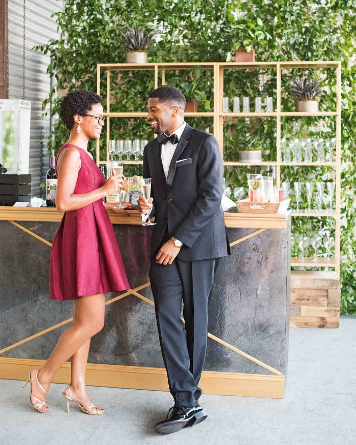 wine red mini dress, worn by a smiling woman, holding a drink and talking to a man, dressed in a smart black suit, cocktail attire for men, with a white shirt, and a black bowtie