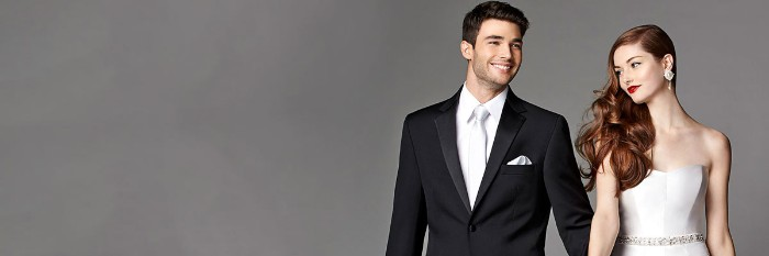 silver tie worn with a white shirt, and a black dinner jacket, with a silver handkerchief, black tie optional, worn by a smiling groom, standing hand in hand with a bride, dressed in a light silver strapless dress