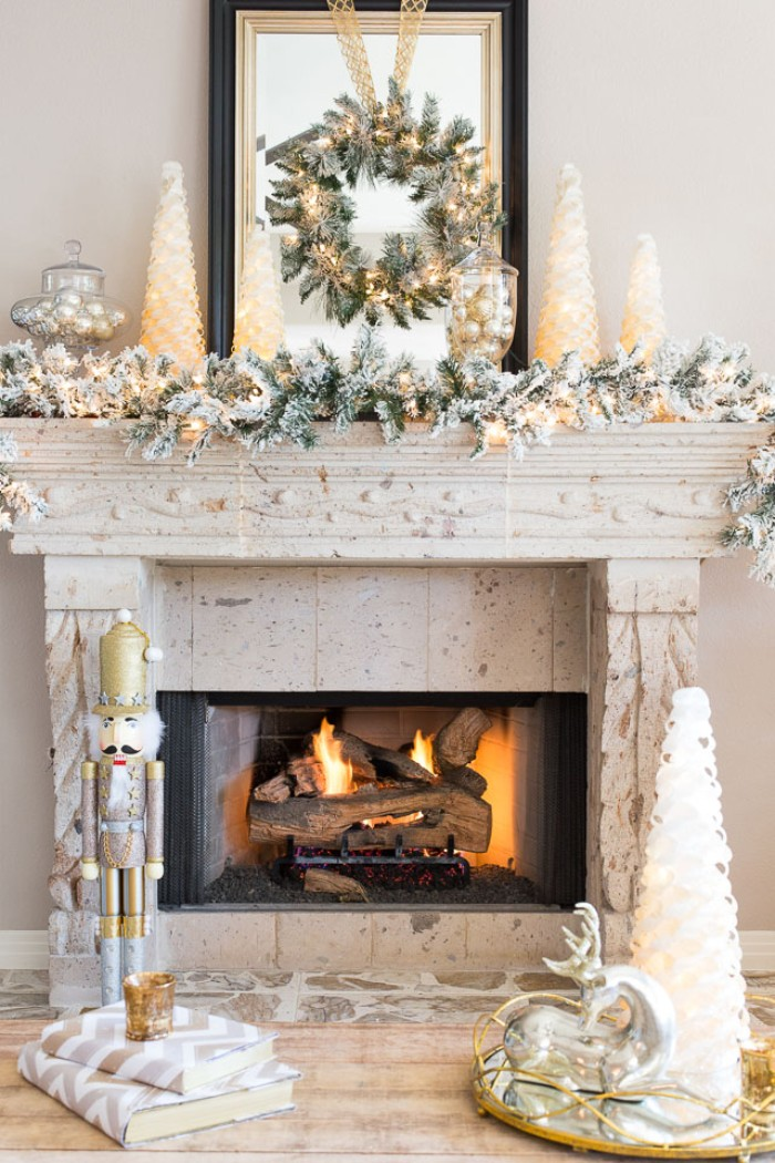 nutcracker ornament and several candles, shaped like christmas trees, on and near, a vintage style stone fireplace, in light cream, fireplace decor, green wreath with glowing fairy lights