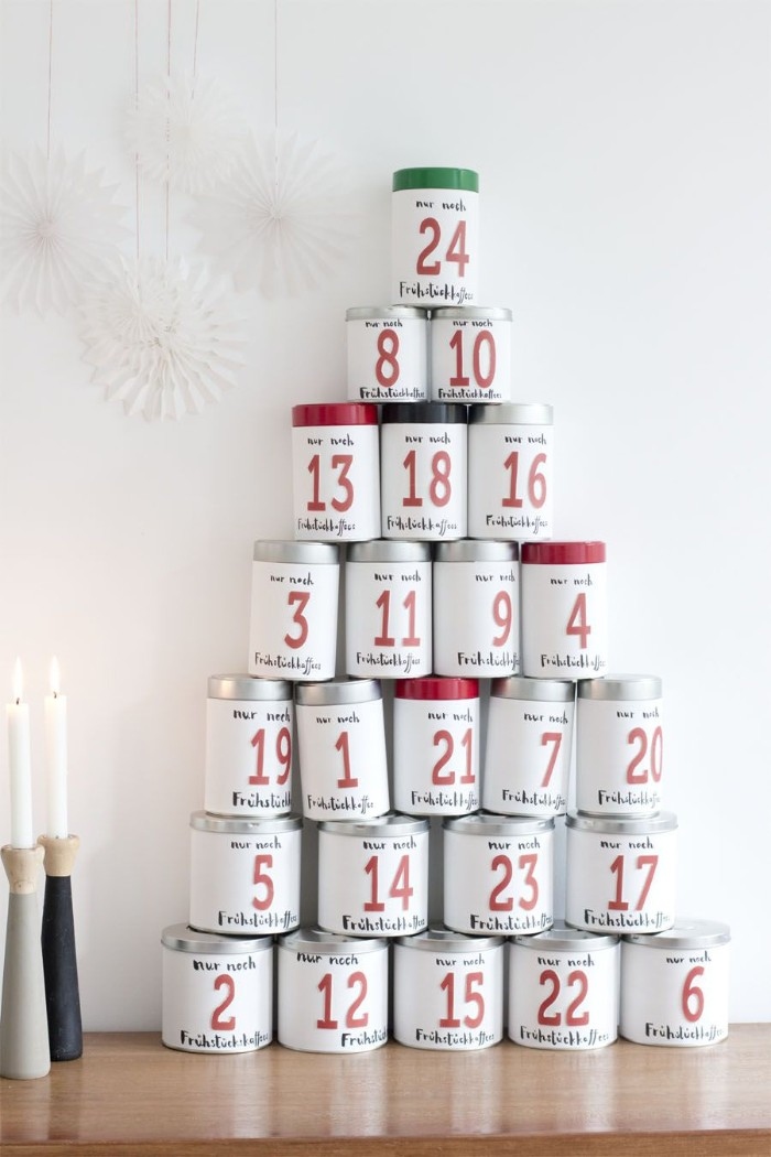 pyramid shape made of white cans, with silver and black, red and green details, fun advent calendars, each can features a number, from 1 to 24, written in red