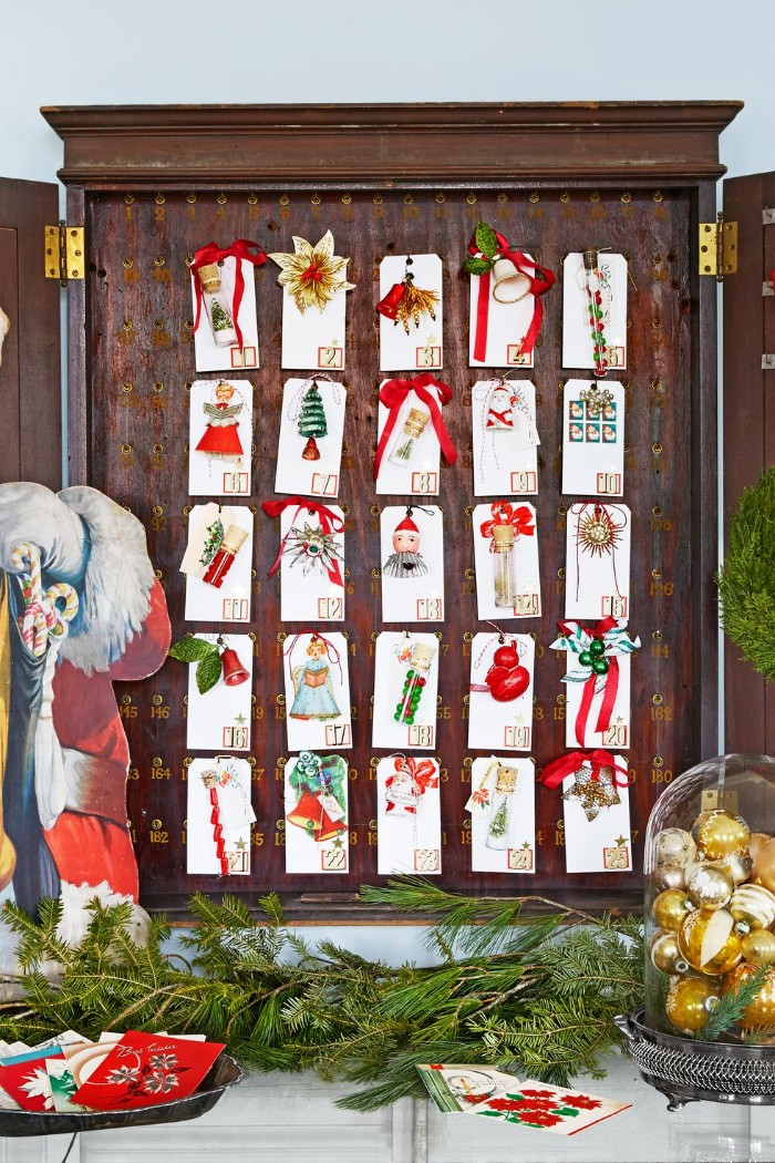 christmas countdown calendar, 25 small numbered white cards, each containing a small christmas tree decoration, placed inside a shallow, wooden cupboard-like structure, surrounded by festive decorations