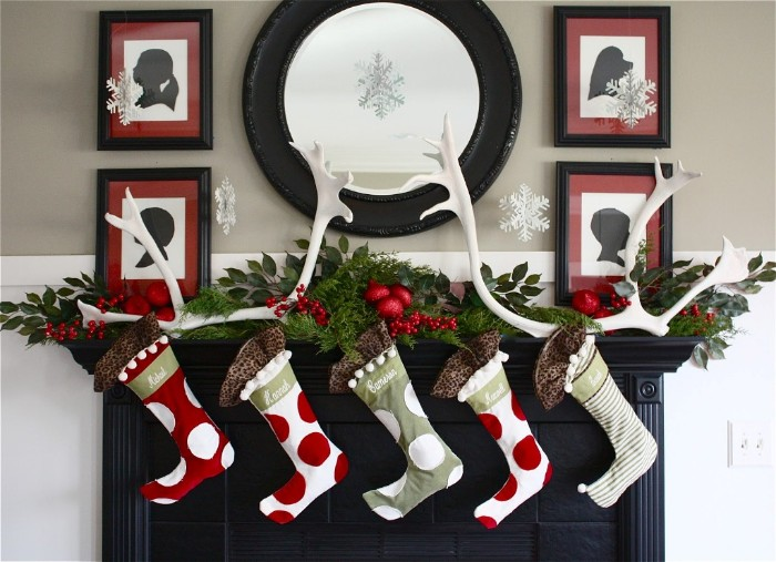 white antlers and five stockings, in red and white and grey, decorated with red and white polka dots, and white and grey stripes, on a christmas fireplace, four framed artworks and a round mirror