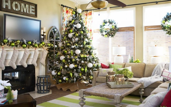 fireplace decor, with five white stockings, and a silver garland, featuring green baubles, christmas tree with similar ornaments, standing nearby