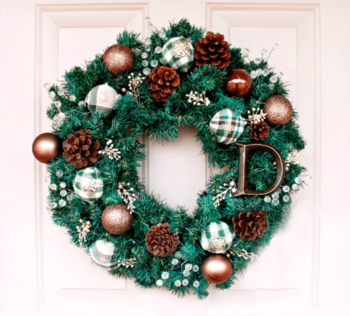 the letter d, decorating a green wreath, made from faux pine branches, adorned with green and white, and bronze-colored baubles, clear plastic berries and pinecones, diy wreath