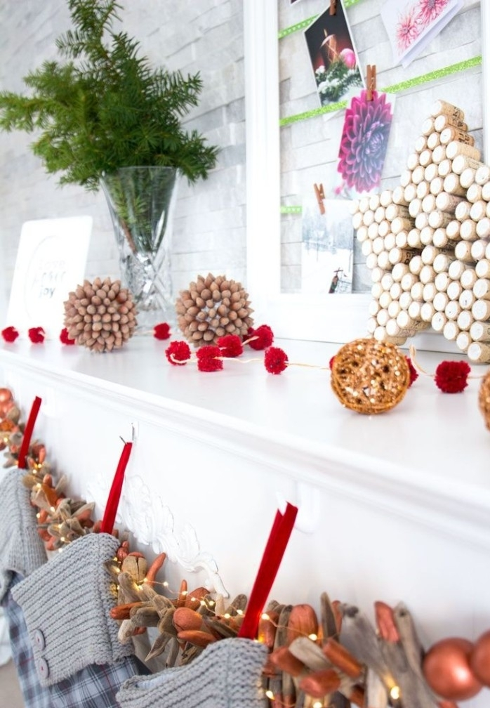 close up to a white mantelpiece, decorated with wooden ornaments, and a garland with small red pompoms, fireplace mantel decor, grey stockings and small fairy lights