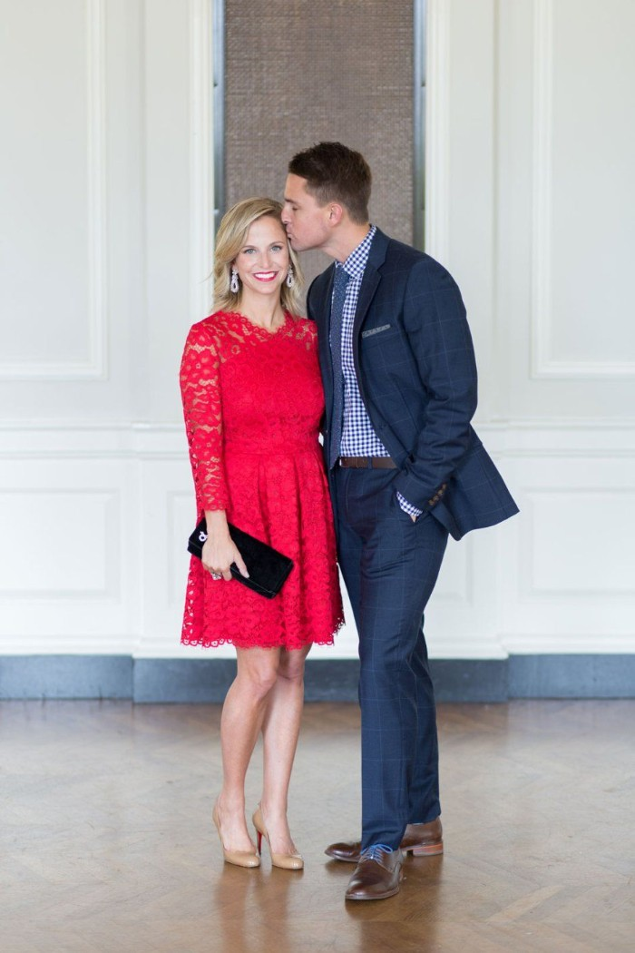 short-haired brunette man, dressed in a navy suit, with a checkered blue shirt, and a dark blue tie, cocktail attire for men, kissing a smiling blonde woman, wearing a red lace cocktail dress