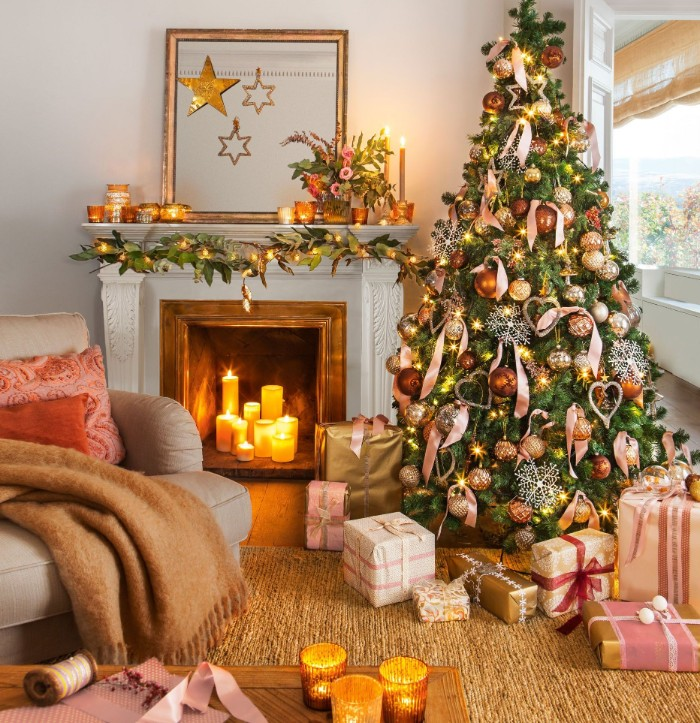 several glowing candles, placed inside a fireplace, decorated with a green garland, and fairy lights, holiday images, lavish christmas tree and presents nearby