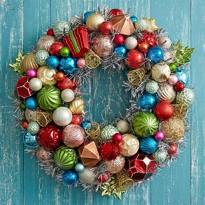 lots of christmas tree ornaments, in various shapes and sizes, glued together to form a wreath, hung on a pale blue door, with chipped paint