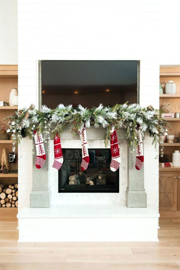 garland made from green, faux pine branches, decorating a christmas fireplace, with five and red stockings
