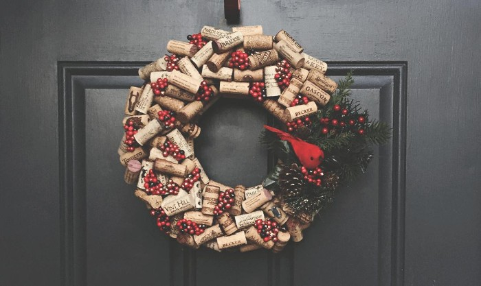 door in black, decorated with a diy christmas wreath, made from cork bottle stoppers, adorned with a small red bird figurine, fir leaves and red berries