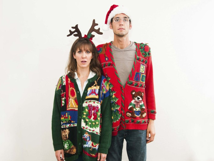 ugly sweater party, couple wearing festive cardigans, in dark green and red, decorated with multicolored motifs, featuring teddy bears, xmas wreaths and others