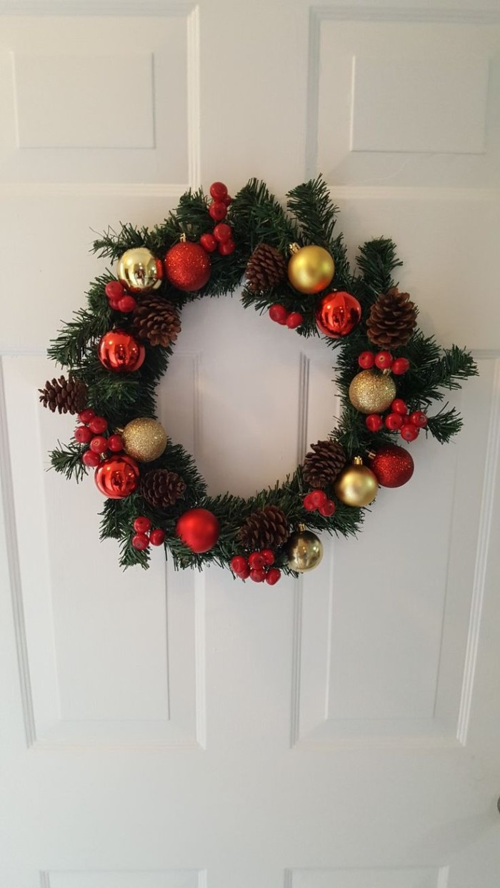 classic christmas wreath, made from fake fir branches, and decorated with red and gold baubles, and large red faux berries
