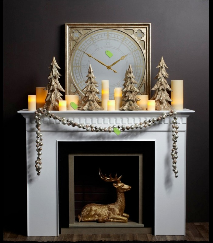 ten faux glowing candles, on a white mantelpiece, next to four christmas tree statuettes, a large antique clock, and a silver garland, reindeer statuette in gold