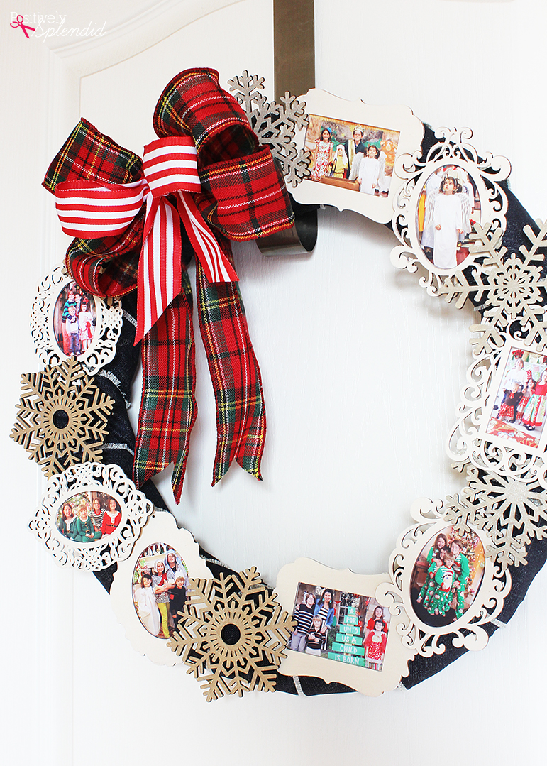 framed family photos, stuck onto a black hoop, to form a christmas wreath, decorated with a large, red tartan bow, and a smaller, striped red and white bow