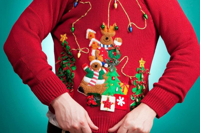 close up of a red jumper, decorated with multiple festive applique details, in various colors, ugliest christmas sweater, reindeer and xmas trees, presents and string lights