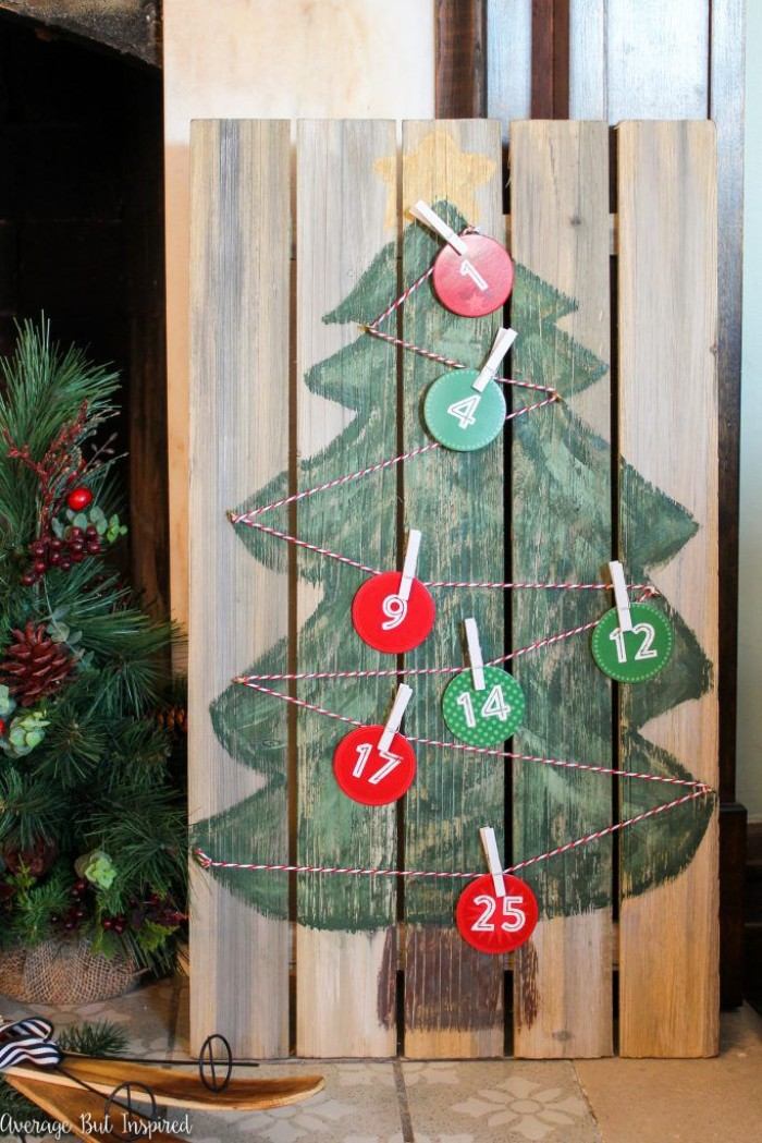pallet made of wood, with a simple, child-like drawing of a christmas tree, decorated with striped, red and white string, featuring round numbered labels, in different colors, attached to the string with clothes pegs, fun advent calendars diy