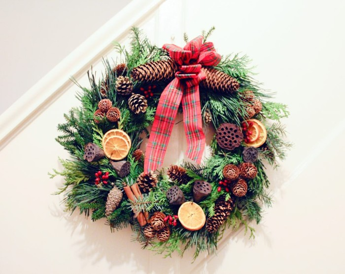 pine cones in different shapes and sizes, cinnemon sticks and small red berries, dried orange slices and lotus pods, on a wreath made from pine leaves, christmas wreath ideas, red ribbon with a plaid pattern on top