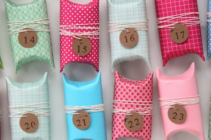 little boxes made from folded toilet paper rolls, decorated with colorful patterned paper, diy advent calendar, small round tages, with different numbers, tied onto each box, with plain string