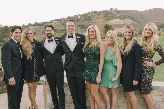 people dressed in smart clothes, smiling and posing for the camera, black tie optional wedding, the women are wearing dresses in green and cream, with black lace details, the men are dressed in black suits, with white shirts, and black bowties