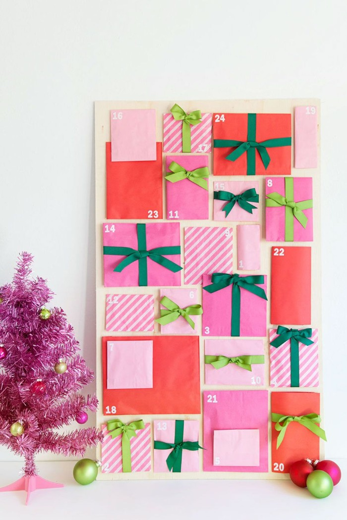 coral red and bubblegum pink envelopes, some with white stripes, in different sizes and shapes, decorated with light, and dark green ribbons, stuck to a rectangular board, fun advent calendars, each envelope has a small white number, from 1 to 24