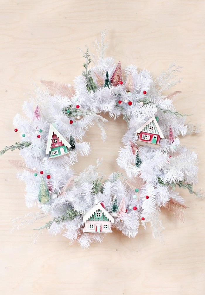 plastic fir branches in white, shaped into a christmas wreath, and decorated with small house figurines, wreath ideas, tiny red and green faux berries