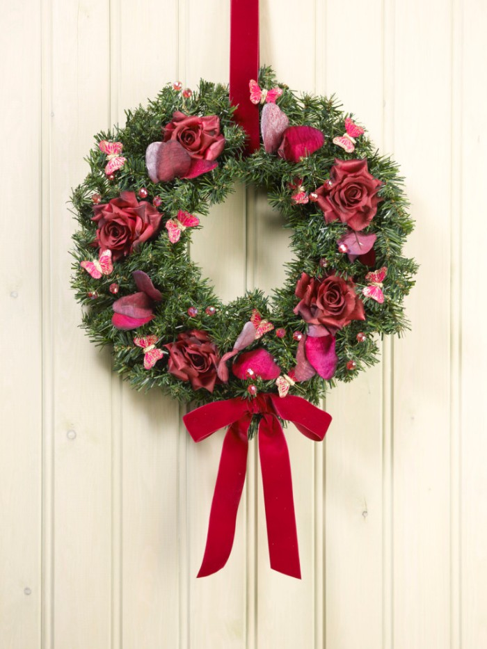 roses in red, most likely fake, decorating a green wreath, made from faux fir branches, and adorned with small pink butterflies, and a red ribbon