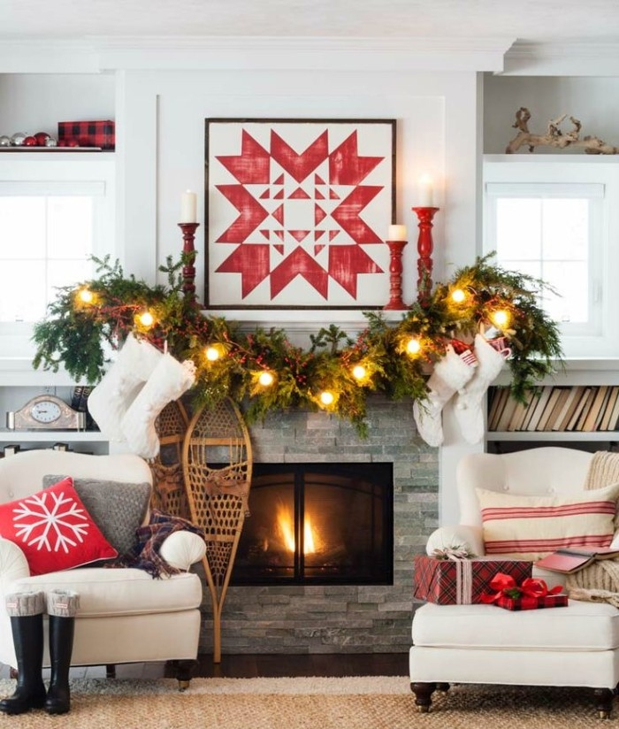 geometric print in red, framed above a fireplace, decorated with a garland, made from pine leaves, and adorned with nine glowing lights, holiday images