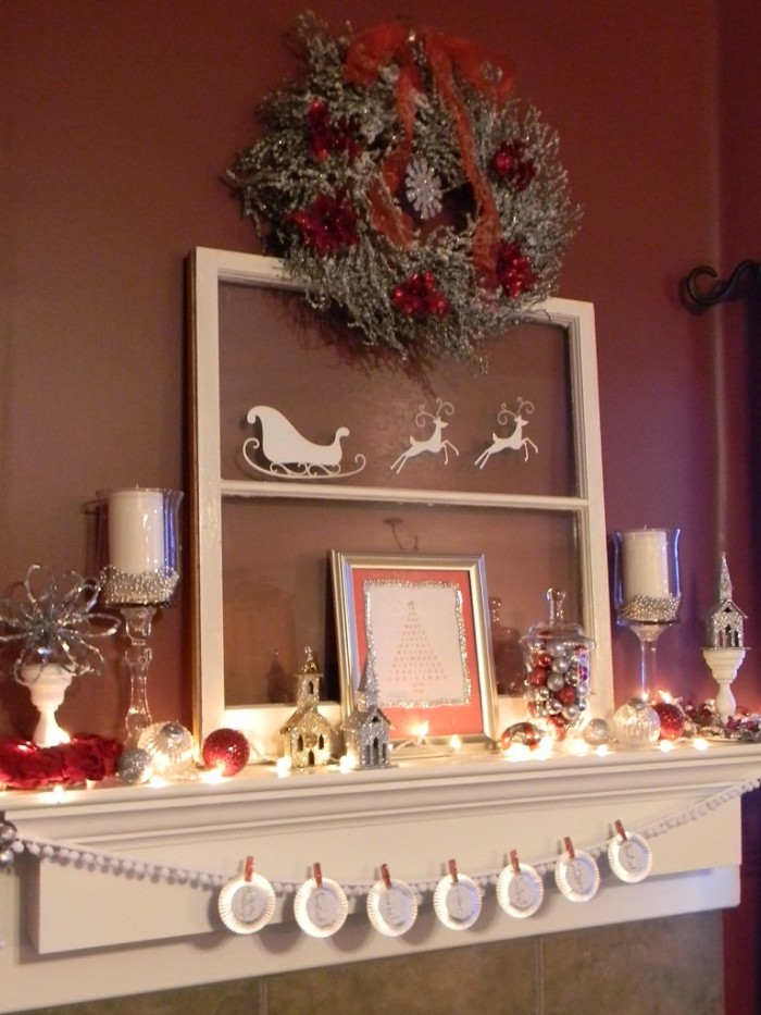 brown wall near a white mantel, decorated with a silver and red wreath, a frame with santa's sleigh and two reindeer, candles and more, diy fireplace mantel ideas