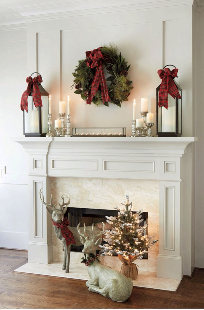 couple of deer statuettes, and a miniature christmas tree, decorated with glowing string lights, near a white and pale cream fireplace, images of christmas, green wreath with a red bow, and burning candles