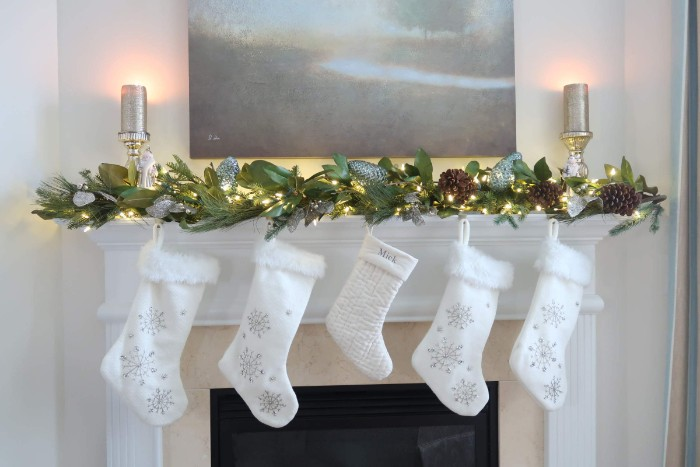 embroidered white stockings, with silver snowflakes, hanging from a mantel, decorated with a garland, made from branches with large green leaves, and lit string lights, mantel decor for your home