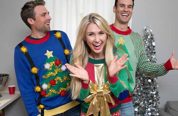 laughing men and a woman, dressed in garish, multicolored festive jumpers, ugly sweater party, christmas tree and present motifs