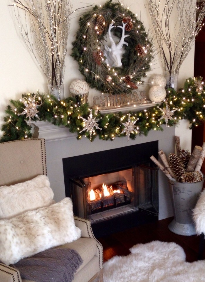 snowflake ornaments covered in silver glitter, and tiny glowing string lights, on a green garland, made from faux pine branches, decorating a grey and black fireplace, in a cozy living room, fireplace decor ideas