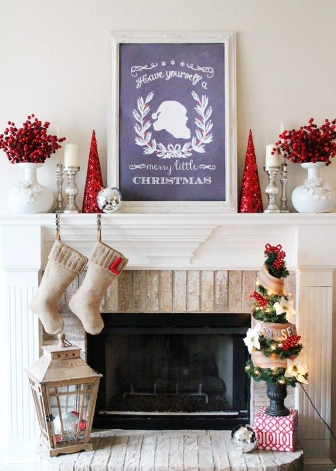 framed blackboard with an image of santa, and a festive message, done in white chalk, on a white mantelpiece, near two cone shaped, christmas tree ornaments, covered in red glitter