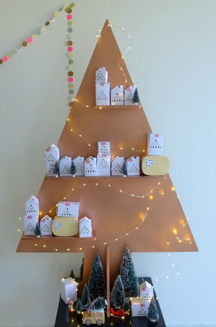 triangular christmas tree decoration, made from beige cardboard, with three shelves, containing small white boxes, advent calendar ideas, small lit string lights, and various decorations