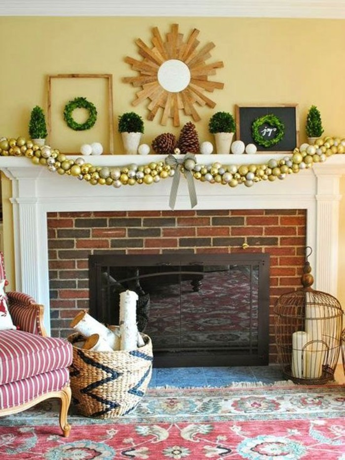 kilim rug in red, green and white, near a brick fireplace, decorated with a gold and silver garland, two gigantic pinecones, two small framed wreaths, white baubles and others