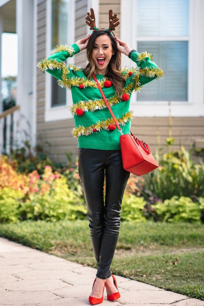 girls ugly christmas sweater, laughing slim brunette woman, with a headband featuring felt antlers, wearing a green jumper, decorated with gold garlands, and red baubles