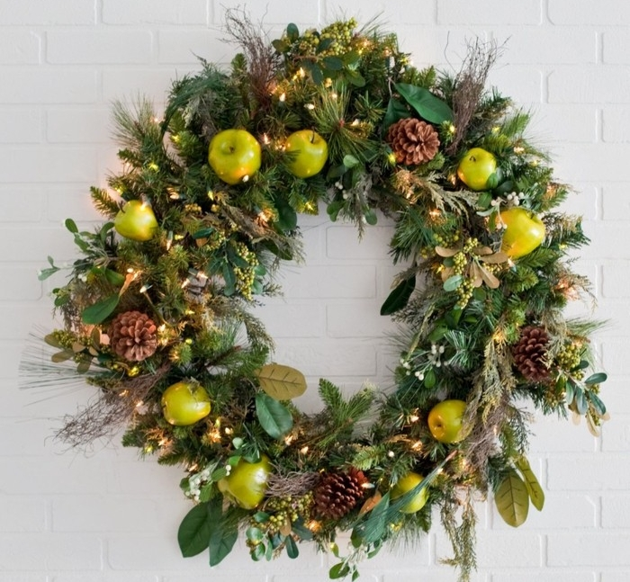 apples and pinecones, and small glowing string lights, decorating a wreath, made from different kinds of leaves, wreath ideas, on a white brick wall