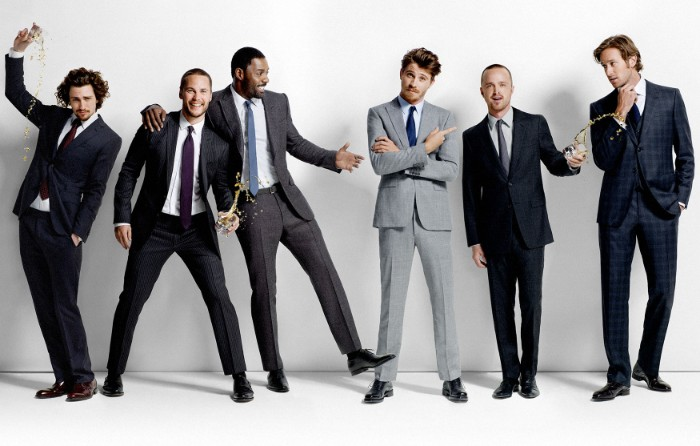 six men dressed in smart suits, in light grey, dark grey and navy blue, cocktail attire for men, smiling and posing for a photo