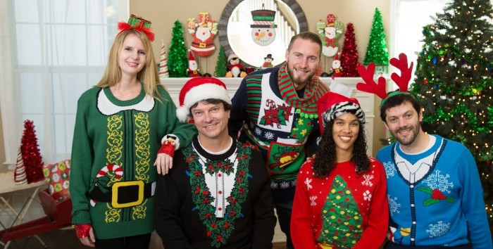 five smiling young people, wearing festive jumpers, in different colors and designs, santa's suit in green, mock tuxedo decorated with holly, ugly sweater ideas, xmas tree and snowflakes